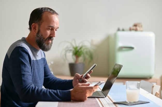 Вид сбоку молодого бородатого мужчины со смартфоном в каждой руке и его ноутбуком на столе многозадачность, перерывы в работе