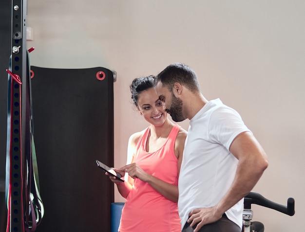 笑顔の若い女性は、ジムで休憩中にひげを生やした若い男に彼女の携帯電話で何かを示しています
