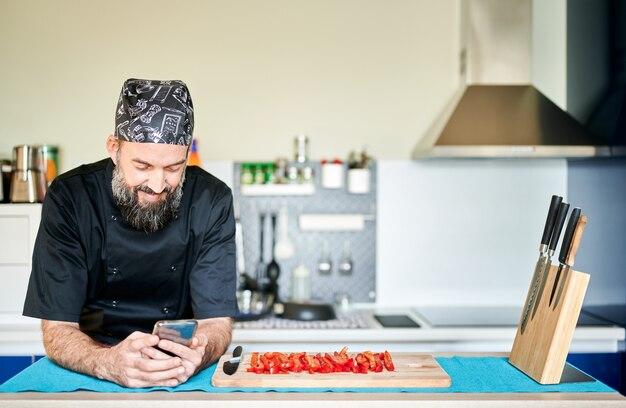 Улыбаясь среднего возраста повар с помощью своего мобильного телефона во время приготовления пищи. он опирается на стол рядом с разделочной доской с красным перцем в полосках.