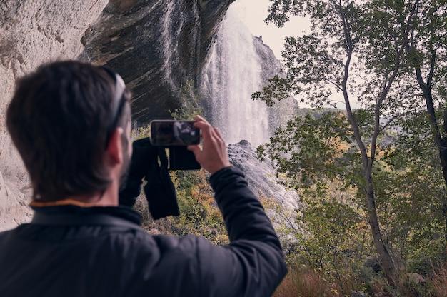 彼のスマートフォンで滝の写真を撮る若い男の背面図。