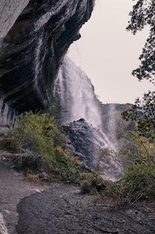 手前の大きな岩の上に水が落ちる滝の景色