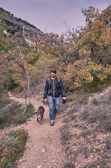 若い男が彼のボクサー犬と一緒に山の中を散歩の正面図