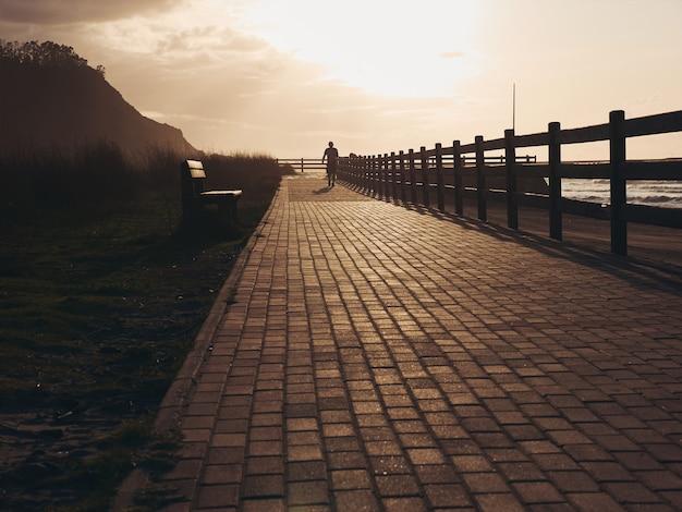 バックグラウンドで歩いている人のシルエットと美しいプロムナードの海岸に沈む夕日
