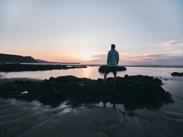 絹のような水と太陽の反射に包まれたいくつかの岩の夕日を見ている少年。
