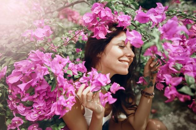 ピンクの花の背景に公園で肖像画の女の子を閉じる