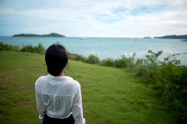 Девушка стоит на холме спиной и смотрит на море