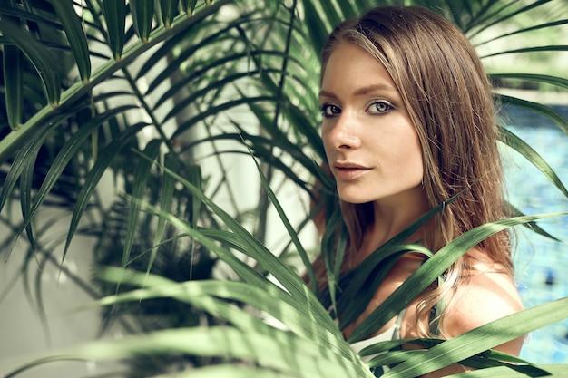 Красивая девушка с листьями тропиков