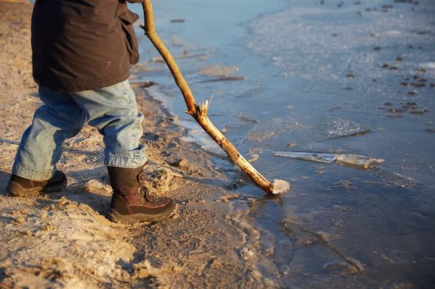 足のクローズアップ小さな男の子が川沿いに立って、長い棒で遊んで