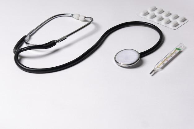 聴診器、温度計、錠剤、白い背景の上