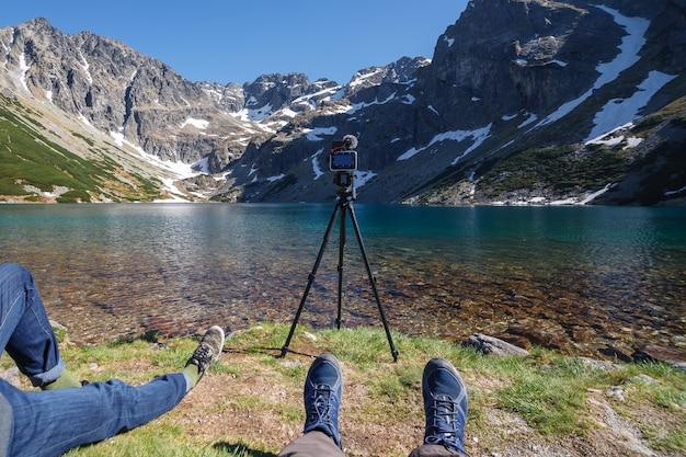 写真家は山の湖の景色を眺める