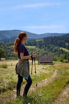 Подходит молодая женщина, походы в горы, стоя на скалистом горном хребте с рюкзаком и полюс, оглядывая альпийский пейзаж