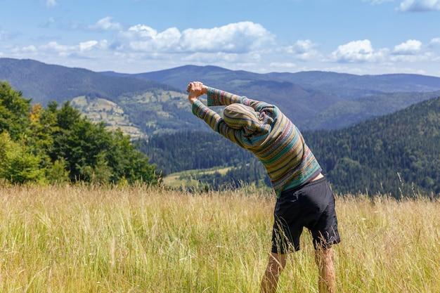 バックパックと高山の風景を見渡すポールと岩の頂上尾根に立っている山でのハイキングに合う若い女性