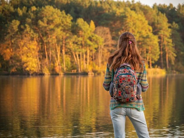 Вид сзади девушка с рюкзаком стоит возле реки