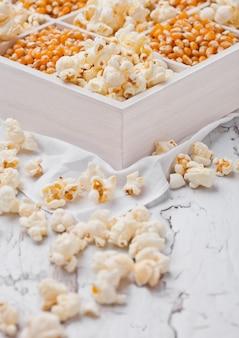 生の黄金のスイートコーンの種子と明るい背景に白い木箱にポップコーン