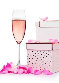 心とピンクのギフトボックスと白い背景のバレンタインデーのバラとピンクのシャンパンのグラス