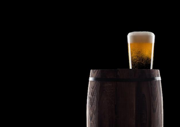 Холодное стекло пива ремесла на старом деревянном бочонке на черной предпосылке с росой и пузырями. с пространством для вашего текста.