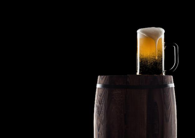 露と泡と黒の背景に古い木製の樽にクラフトビールの冷たいガラス。テキスト用のスペース。
