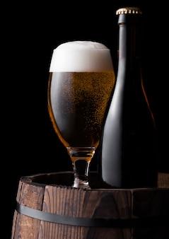 Холодная бутылка и стакан крафтового пива на старой деревянной бочке на черном фоне