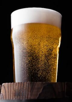 Холодное стекло крафтового пива на старой деревянной бочке на черном фоне