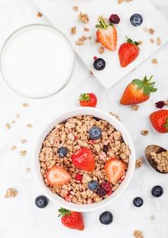 イチゴとブルーベリーと大理石のボード上のミルクのガラスと健康的なシリアルグラノーラのボウル