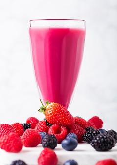 Стакан молочного коктейля со свежими летними ягодами смузи