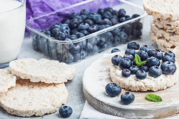 リコッタチーズと新鮮なブルーベリーと明るい石のキッチンでミルクのガラスと健康的な有機餅。上面図。いちごのプラスチックトレイ