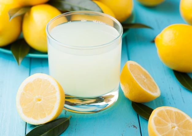 青い木製の生レモンと有機の新鮮なレモンジュースのガラス