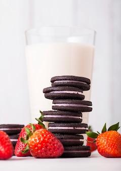 Клубничное темное печенье со стаканом молока и свежими ягодами на деревянном столе