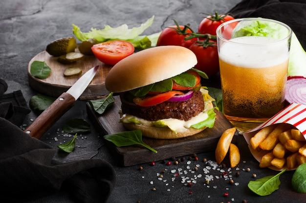 Свежий говяжий бургер с соусом и овощами и бокалом лагерного крафтового пива с картофелем фри на каменной кухне.