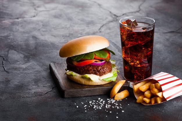 石造りのキッチンでポテトチップスポテト添えソースと野菜とコーラソフトドリンクのガラスと新鮮な牛肉のハンバーガー。