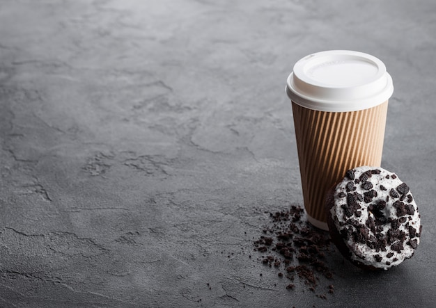 黒い石のキッチンテーブルに黒いクッキードーナツと段ボールのコーヒーカップ。カフェドリンクとスナック。