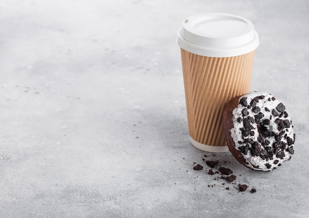 石のキッチンテーブルの上の黒いクッキードーナツと段ボールのコーヒーカップ。カフェドリンクとスナック。