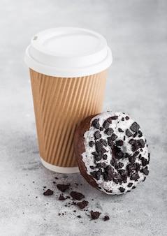 石造りのキッチンに黒いクッキードーナツと段ボールのコーヒーカップ。カフェドリンクとスナック。