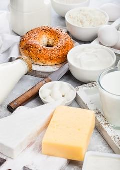 ヴィンテージの木製の箱で新鮮な乳製品。瓶と牛乳のガラス、サワークリームとチーズと卵のボウル。ナイフで丸いまな板に焼きたてのベーグル。
