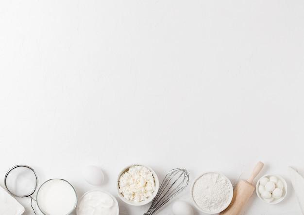 白いテーブルに新鮮な乳製品。牛乳のガラス、小麦粉のボウル、サワークリーム、カッテージチーズ、卵。鋼の泡立て器と麺棒。
