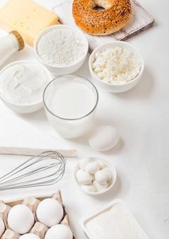 Свежие молочные продукты на белом столе. стакан молока, миска муки и творога и яиц. свежий запеченный бублик с ножом. стальной венчик.