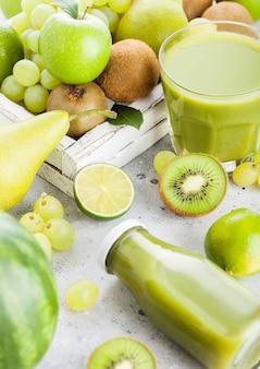 ガラスと石造りのキッチンの白いビンテージボックスで有機グリーントーンフルーツと新鮮なスムージーのボトル。梨とブドウとキウイ、ライムとリンゴ。