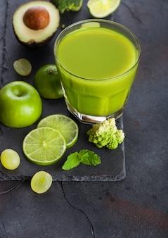 新鮮な生の有機緑のトーンの果物と野菜のガラス。アボカド、ライム、リンゴ、キウイ、ブロッコリーとカリフラワーのブドウ