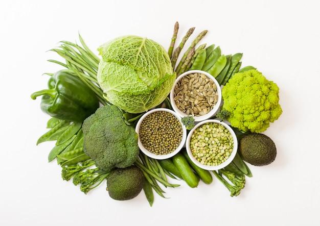 グリーントーンの生の有機野菜の盛り合わせ。アボカド、キャベツ、ブロッコリー、カリフラワー、キュウリ、トリムド豆、リョクトウ豆、パクチョイ、ルースパッパー、レタス