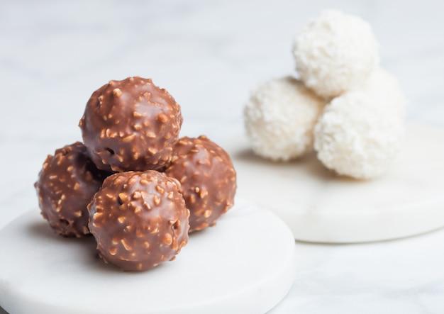 Роскошные шоколадные конфеты с фундуком и белыми сливками с кокосовой стружкой на мраморном столе.