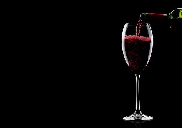 Лить красное вино из бутылки в бокал изолированы