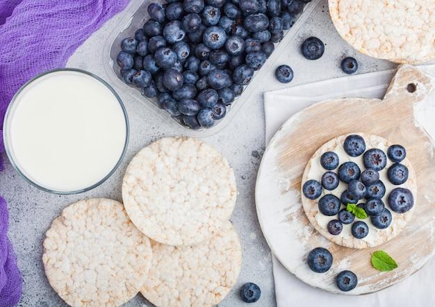 リコッタチーズと新鮮なブルーベリーと牛乳のガラスの健康的な有機餅
