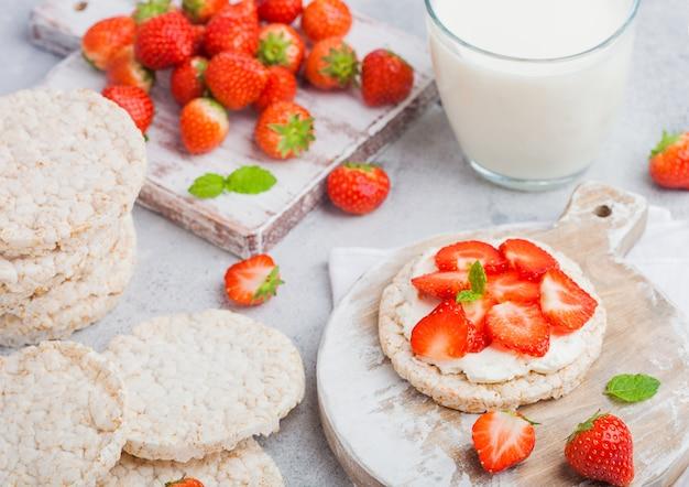 木の板と牛乳のガラスにリコッタチーズと新鮮なイチゴの健康的な有機餅