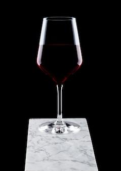 Стакан красного вина на белой мраморной доске на черном фоне