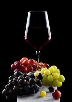 Бокал красного вина с виноградом на черном фоне