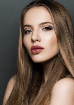 暗い背景に長い髪の美しい女性モデルの肖像画。赤い唇