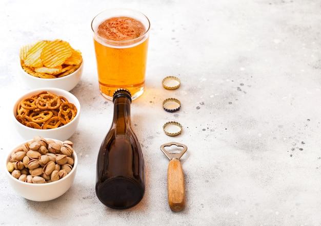 Стекло и бутылка ремесленного лагерного пива с закусками и открывашкой на каменном кухонном столе