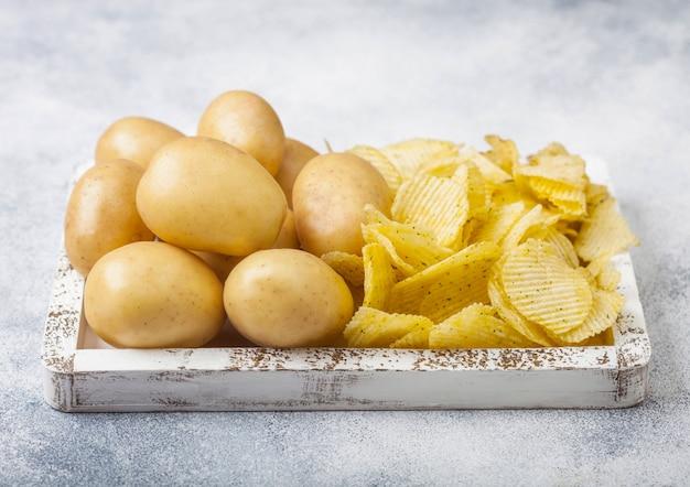 新鮮な有機自家製ポテトチップスチップスライトキッチンテーブルの上の白い木箱に生の黄色いポテト