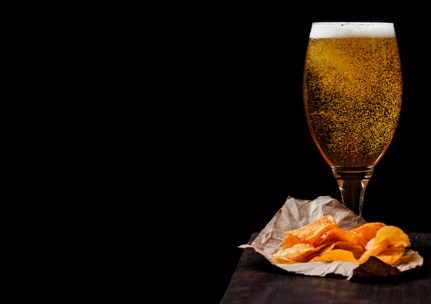 Стекло пива лагера с закуской чипсов картошки на винтажной деревянной доске на черной предпосылке.