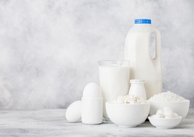白い背景の上の新鮮な乳製品。牛乳のガラス瓶、サワークリームのボウル、カッテージチーズ、小麦粉とモッツァレラチーズ。卵とチーズ。